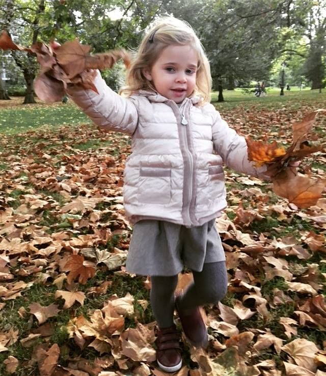 Princess Leonore of Sweden playing in the leaves in a London park.
