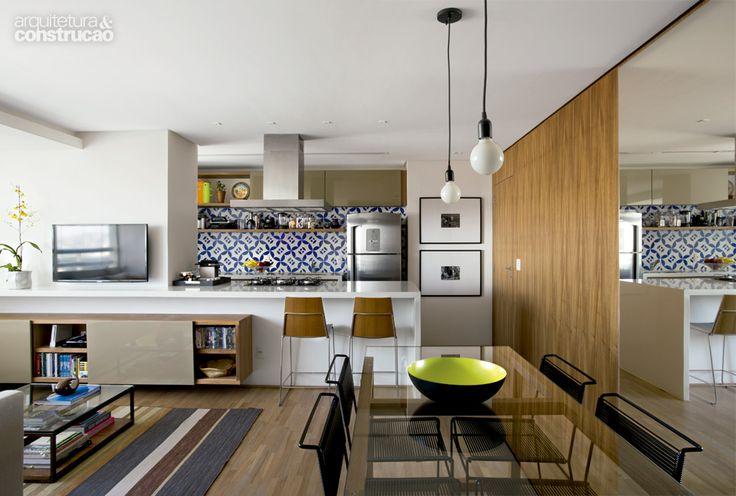 As boas ideias deste projeto: azulejos portugueses na parede da cozinha, a bancada  abraça a parede e serve de rack para a TV, o piso é único, o espelho dá profundidade ao ambiente e o gesso não leva molduras.