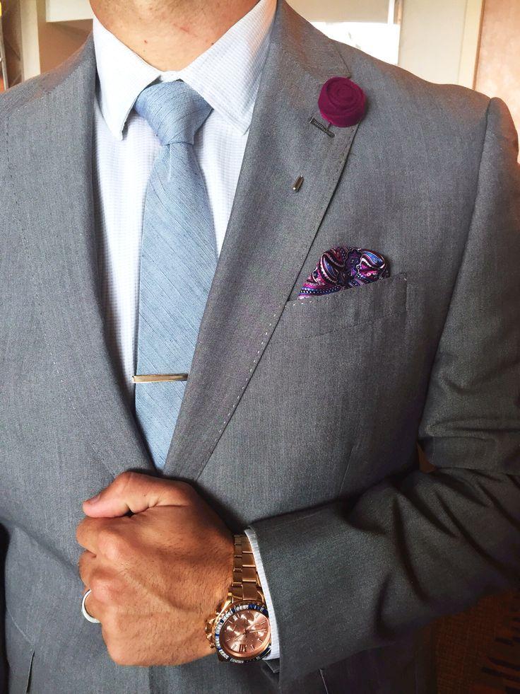 Slate grey suit, white shirt, sky blue tie with tie bar, plum color lapel flower, blue and plum print pocket square.