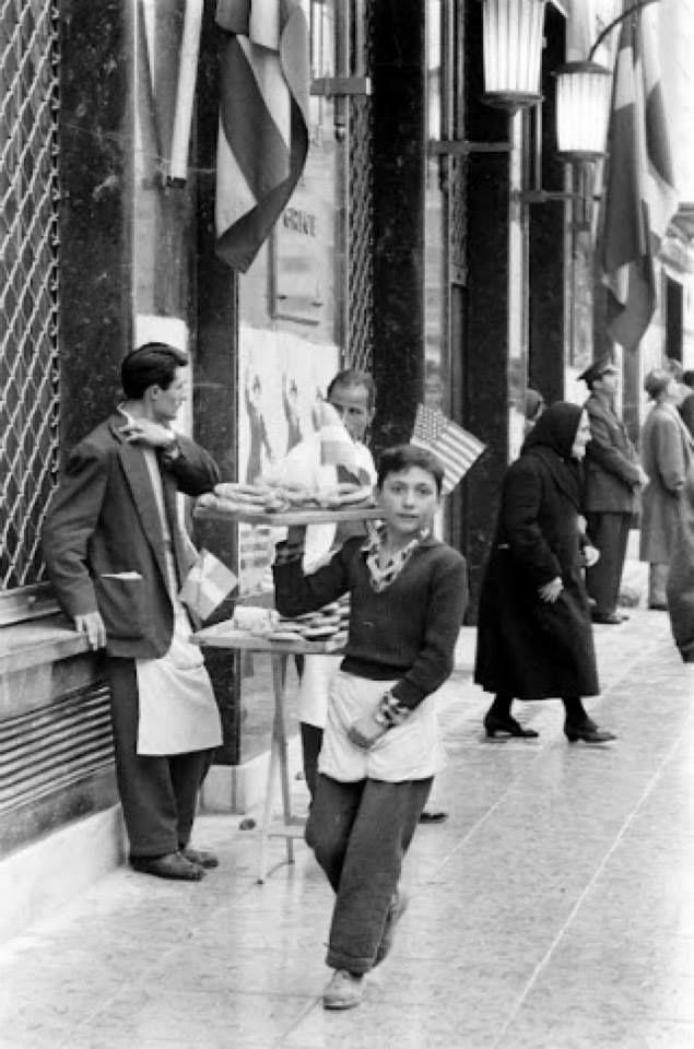 15/12/1959. Μικρός κουλουρτζής στην οδό Πανεπιστημίου 2 έξω από το κτήριο της Εμπορικής Τράπεζας. Ημέρα της επίσημης επίσκεψης του προέδρου της Αμερικής Dwight David (Ike) Eisenhower. (εξ ου και οι Αμερικάνικες σημαίες).
