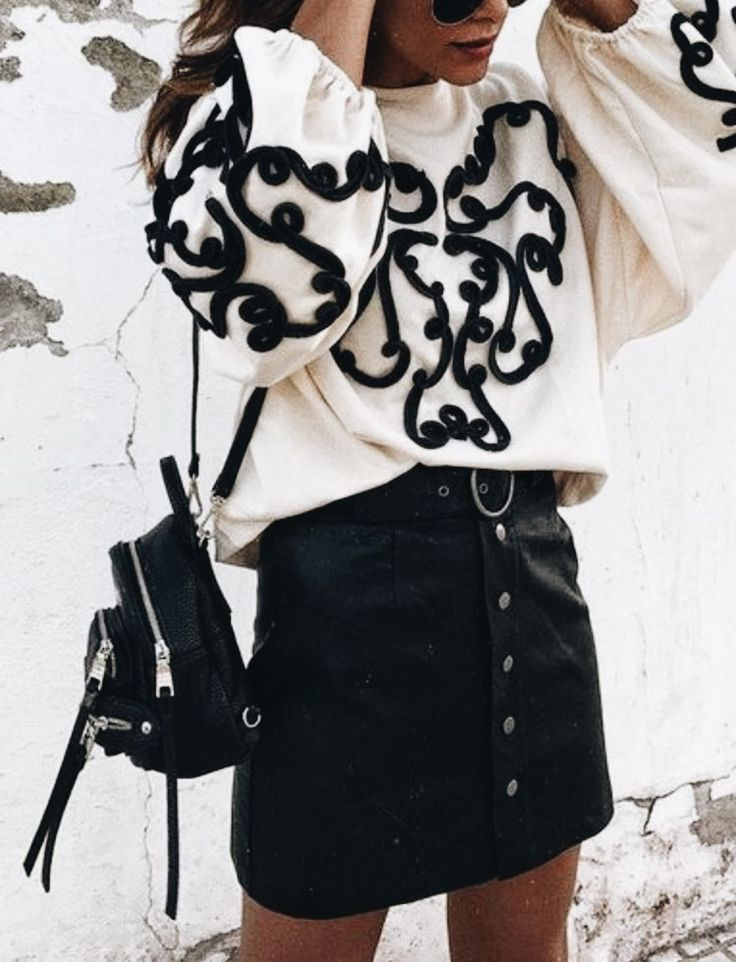 Black and white outfit with button up skirt and white sweater with black arabesque like design. #blackandwhite #womensfashion