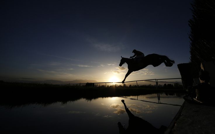 A general view as a runner clears the water jump in The Running Hare Handicap Steeple Chase at Leicester racecourse