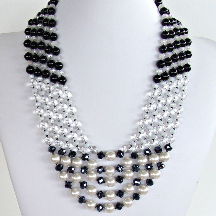 This striking black and white statement necklace is five strands of semi-precious onyx, rock crystal, Swarovski glass pearls and crystal. Full length 25″. Buy this bold one-of-kind piece today.