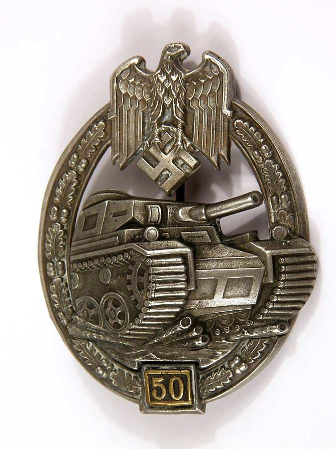 Army /Waffen SS Panzer Assault Badge in Silver for 50 engagements by Gustav Brehmer. This badge features a silver wash with a separately attached 50 engagement front plate. The panzer and Wehrmacht eagle display excellent detail in their design. The reverse reveals typical hollowback construction with a separately attached plate that is affixed with hollow rivets that hold the panzer and 25 plate.