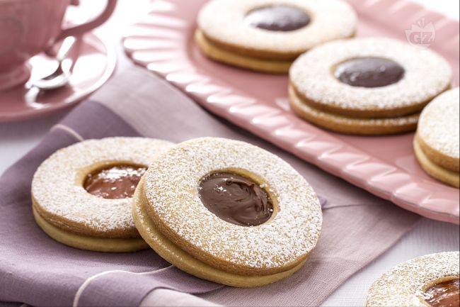 I biscotti occhio di bue sono dei deliziosi dolcetti di pasta frolla con un morbido ripieno di marmellata, ideali per una merenda sfiziosa.
