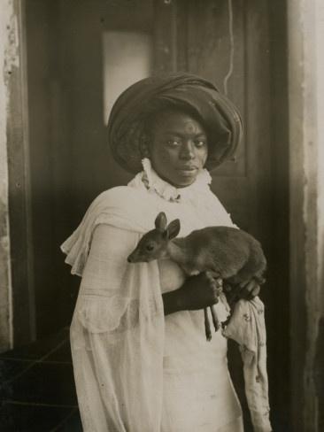 A stylish young Kenya woman holding her pet goat. Underwood and Underwood 1909. Mombassa, Kenya.