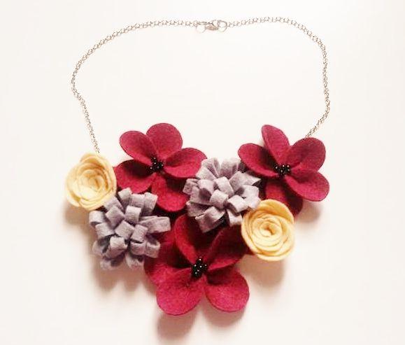 Collar de flores de fieltro en tonos grises, beige y granates.
