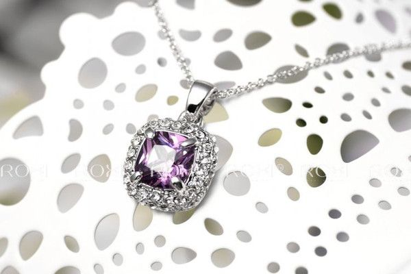Timeless beauty radiates from thissparkling amethyst necklace. Gemstones issurrounded by shimmering crystals. The necklace dangles off an 20inch silver rolo
