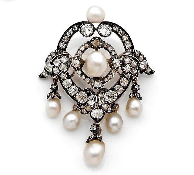 BROCHE  en argent et or 14K formée de deux anneaux, l'un agrafé de feuillages, l'ensemble serti de diamants taille ancienne, orné au centre et en pampilles de 7 perles fines. (Percées). L'épingle en or 18K adaptable. Fin du XIXème siècle. Haut. : 5,5 cm. Poids brut : 15,2 g. Dans son écrin sabot.  A NATURAL PEARL, DIAMOND, 14K WHITE GOLD AND SILVER BROOCH, LATE XIXTH CENTURY.