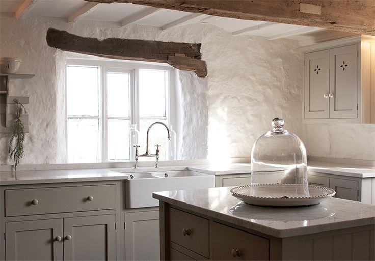 A Silestone worktop in 'Lagoon' surrounds a double sink which floods with natural light from the window behind in this deVOL Kitchen