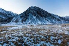 Glen Aspin walks past an icy peak during an ice climbing trip in a series of hidden valleys near Hanmer, Marlborough, New Zealand.