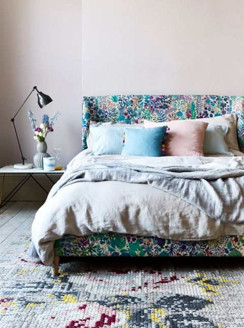 Drift away on a verdant upholstered bed that cannot fail to take centre stage in the room. An abstract rug and plain bed linen add a modern edge to the floral scheme. Find more inspiration at housebeautiful.co.uk. (Photography: Rachel Whiting)
