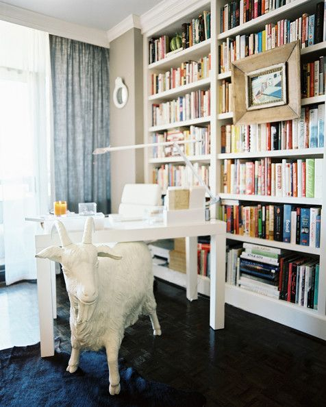 A white goat statue adds some funky flare to an office space with built-in bookshelves.