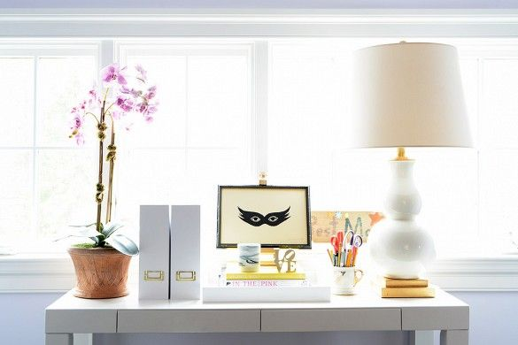 Parsons desk by window styled with orchid, large lamp, and framed art.