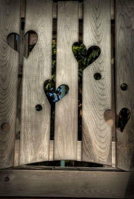 Деревянный забор с вырезанными сердцами.