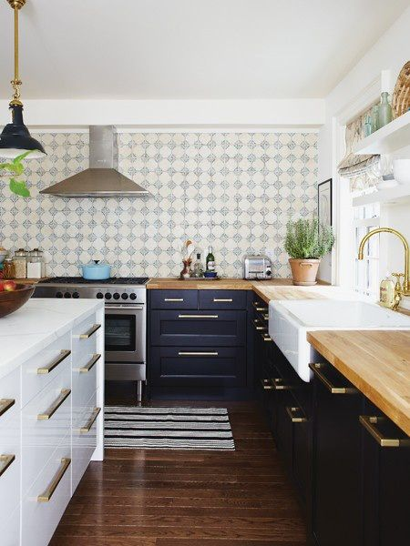 dark lower cabinets with brass pulls, butcher block countertops, white kitchen island, farmhouse sink and light fixtures, tiled wall, terracotta with herbs, wood floors, no upper cabinets, no clutter. Perfect.