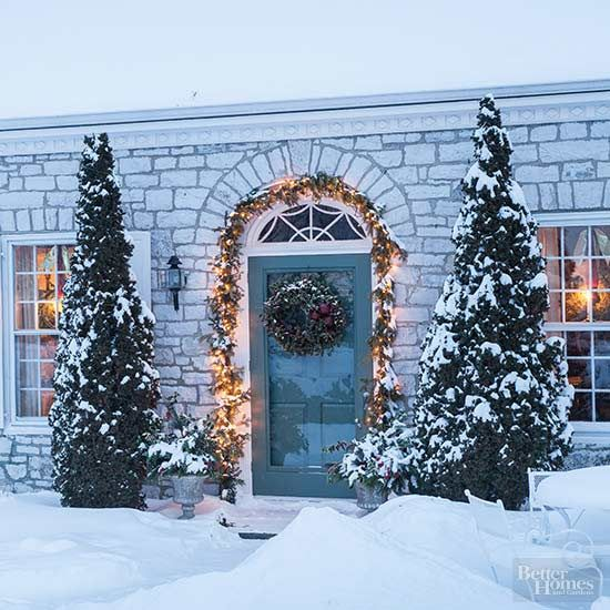 Artfully drape a lit arch above your doorway to create a welcoming Christmas display. Adding evergreen to your traditional holiday lights will add extra sparkle to your Christmas curb appeal./