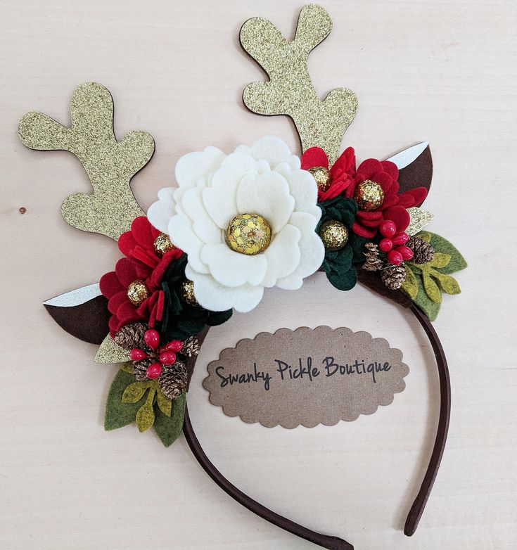 This listing is for a gorgeous reindeer antler headband made with wool felt flowers, gold glitter reindeer ears, sequin glitter balls, mini pine cones and two tone green leaves. The flowers and ears are attached to a plastic satin covered headband in chocolate. The headband