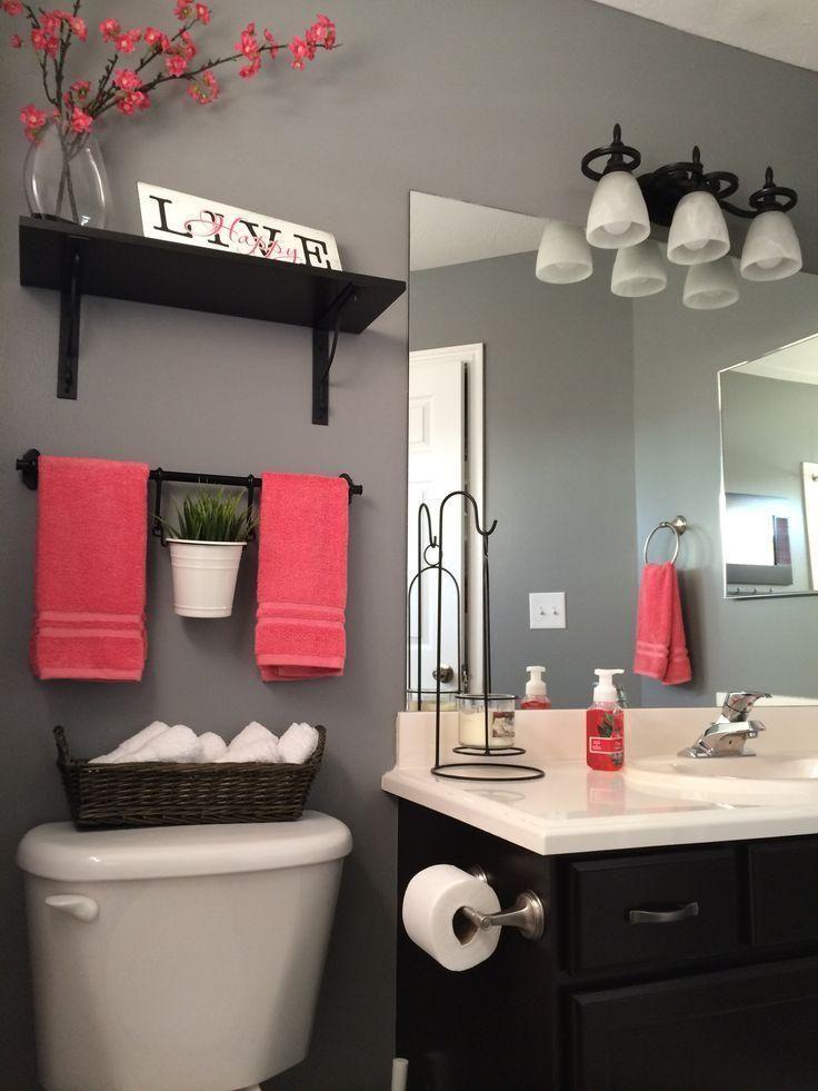 stunning coral color design in bathroom also beige granite countertop vanity sink also towel rack above hand towel shelf as well wall lighting over mirror