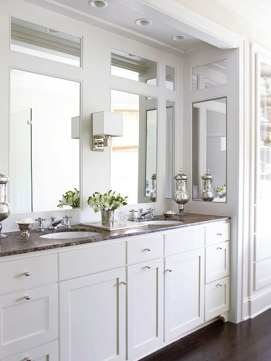 The clean and classic style the homeowners envisioned was achieved using white paint, marble, and vintage-inspired fixtures. Bumping out a wall in the bathroom created extra space that the homeowners filled with a dual vanity. Side mirrors pull double-duty by reflecting light and concealing deep medicine cabinets that contain outlets for hair dryers and shavers.