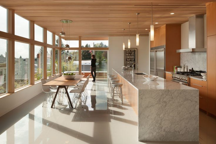 Carrara marble countertop and Minka Lavery mini-pendant lights in kitchen of Seattle home by JW Architects