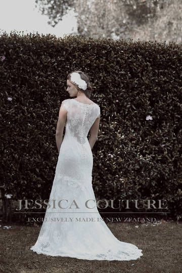 Dress: Celena. Rich French corded lace with an illusion neckline, in a soft fit-n-flare that kicks out into a scalloped hemline with a sweep train. This gown features a very deep open back with covered sheer lace back design, and buttons down the back closure line.