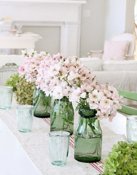 Tafel dekken met groene vaasjes en roze bloemen   Tafeldek-tips: http://www.jouwwoonidee.nl/feestelijke-tafel-dekken-met-eigen-accessoires/