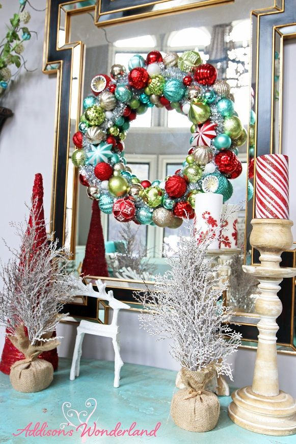 A Holiday accent table vignette adds a fun pop of color to a living room wall. A bright ornament wreath and Christmas accessories from HomeGoods creates the wow factor!  Sponsored by HomeGoods.