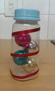 Sensory bottle - Christmas theme -  Bottle filled with baubles and a ribbon wrapped around.