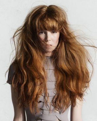 Ultra sleek fringe goes along with hair curled on the sides.