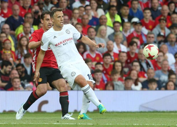 Gary Neville of Manchester United in action with Phil Neville of Michael Carrick AllStars during the Michael Carrick Testimonial match between...