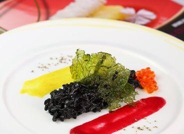 Risotto al nero di seppia ai sentori di bergamotto, granchio, uova di salmone, pepe bianco, salsa di barbabietola e curcuma