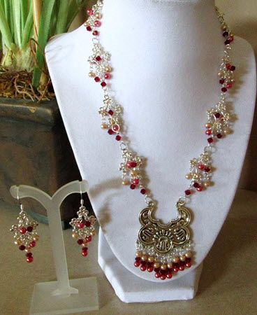 This Oriental-style silver pendant has pink pearls, rose pearls and maroon crystals dangling both from the pendant and from the diamond-shaped silver links in this single strand necklace and earrings set.