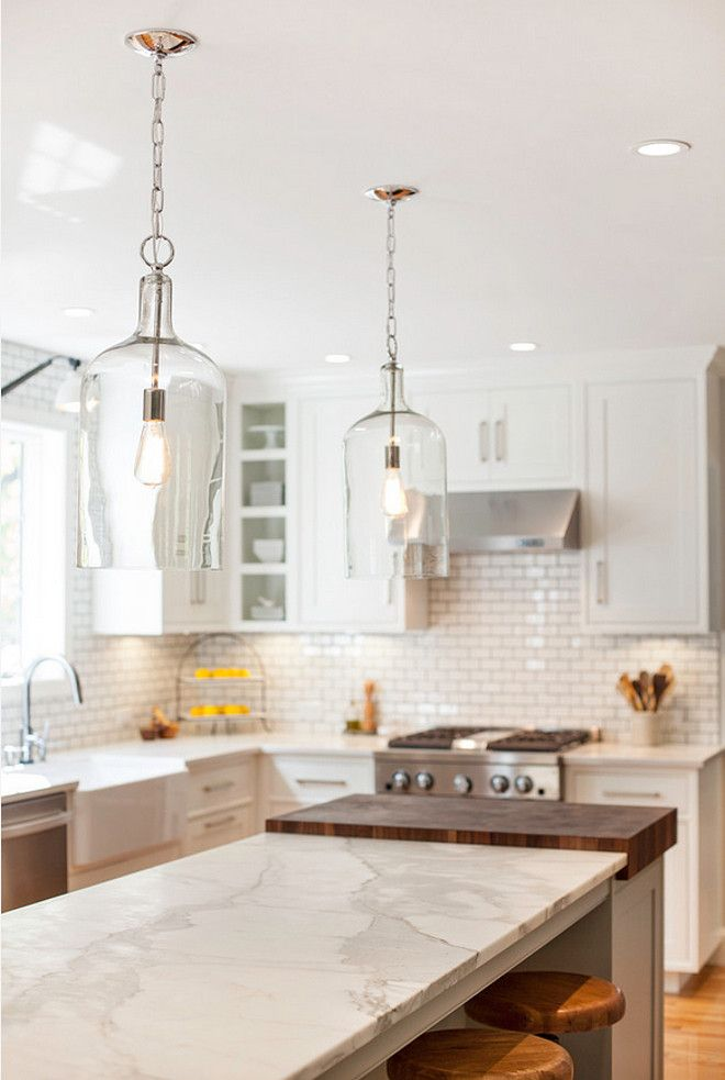 Modern Farmhouse Kitchen DesignThe light fixture above the island is the Glass Jug Lantern from Shades of Light – $179 each.
