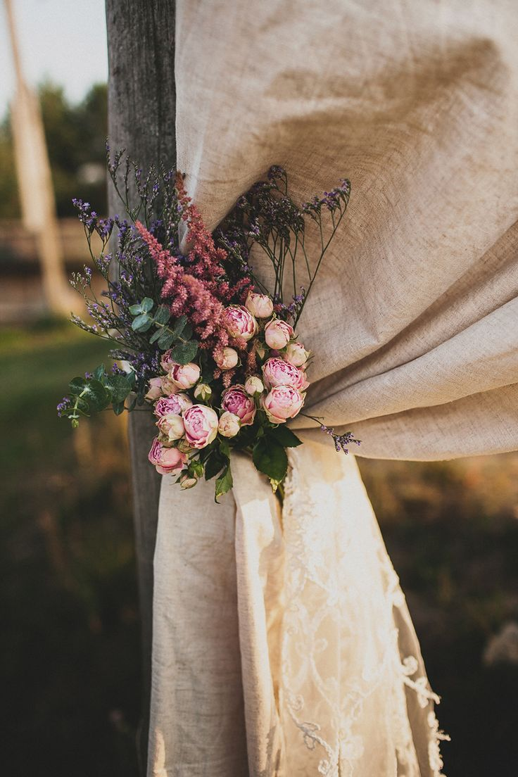 Rustic linen curtain tied back with garden roses, astilbe and statice