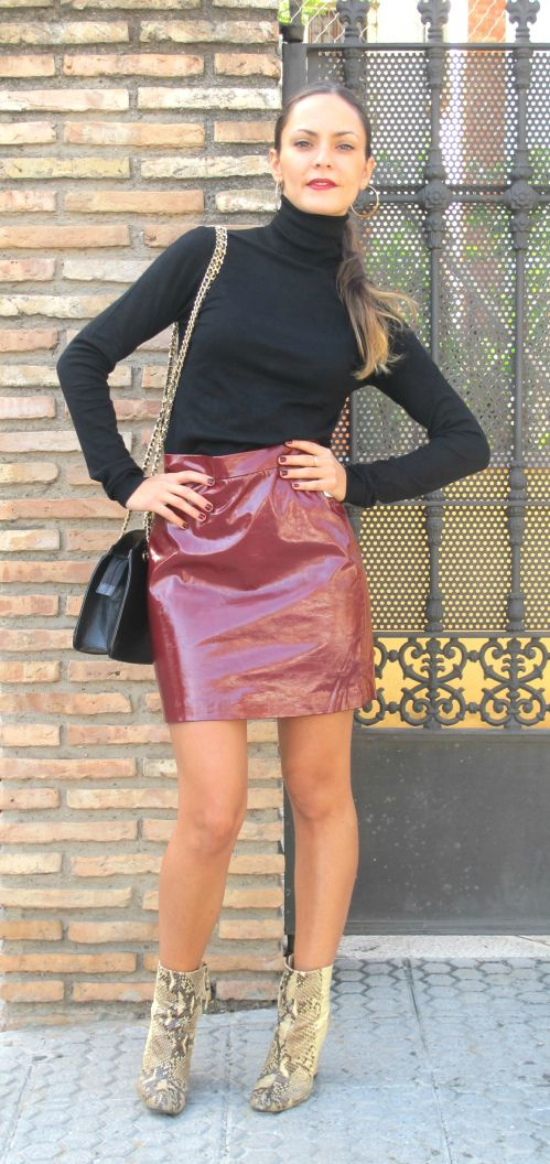 Falda mini de cuero en granate, jersey cuello de cisne en negro, botines piel de serpiente y bolso negro vintage