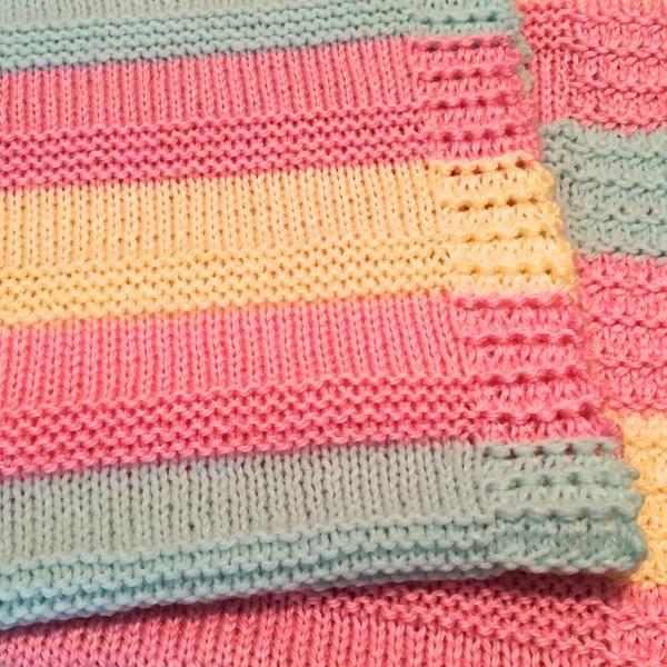 Cheery, hand knit baby blanket, made with 100% acrylic yarn