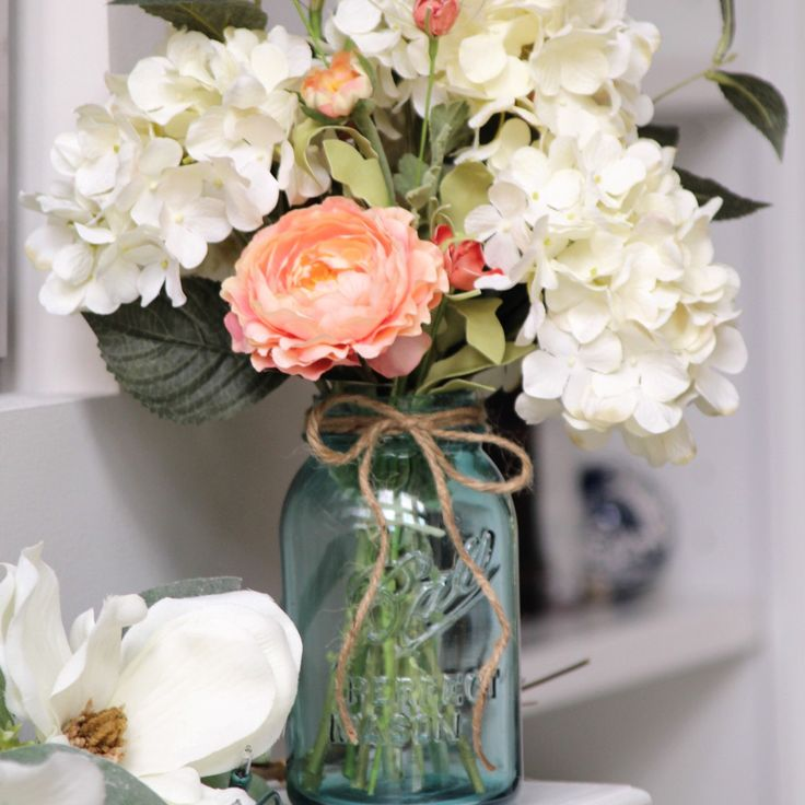 Blue Vintage mason Jar filled with creamy white hydrangeas and coral ranunculus.