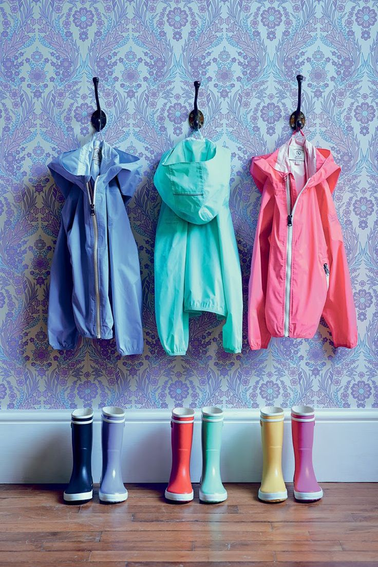 pretty patterned wallpaper with simple single hooks for colorful family outerwear makes for a nice entryway | Aigle