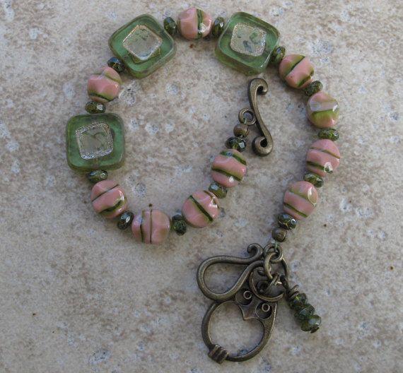 Esta pulsera toda está hecha con cuentas de vidrio checo, hasta los granos de espaciador de pequeño oliva oliva. Tuve que cavar a través de mi escondite para encontrar el cuadrado perfecto los granos para que coincida con la adorable rosa y verde a rayas de granos checos. ¡Me encanta esta pulsera! ¡Agarrarlo antes de decida pertenece en mi armario! La pulsera es rematada con un cierre de palanca y encanto adorable buho bronce y rondelles más verdes oliva! ¡Qué lindo! 7.25 el tamaño (medida)…