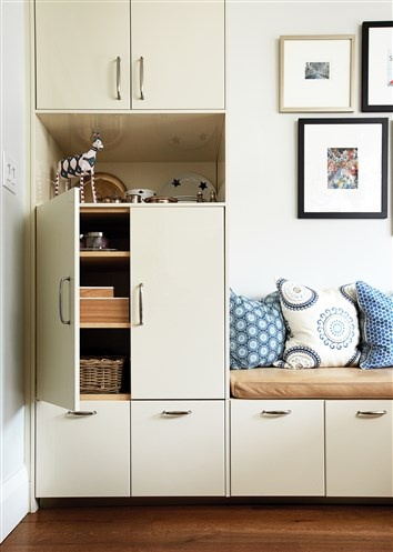 Drawers within reach of children make parent-approved snacks readily accessible to little hands, while a higher-up cupboard makes the perfect mini-bar. Install a bench on top of the cabinets to maximize seating without losing storage space. Dress it up with cosy cushions and place a table in front for extra dining space!