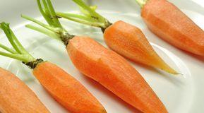 Die Karotten waschen, dünn schälen und etwa 3-4 cm vom Grün stehen lassen. Anschließend nebeneinander liegend in einen Sous Vide Vakuumbeutel geben.Das obere Drittel der Zitronengrasstangen entfernen und den Rest der Länge nach halbieren, dann zu den Karotten geben. Den Ingwer waschen, in dünne Scheiben schneiden und gleichfalls zufügen. Dann das Gemüse mit dem Salz und Zucker bestreuen.
