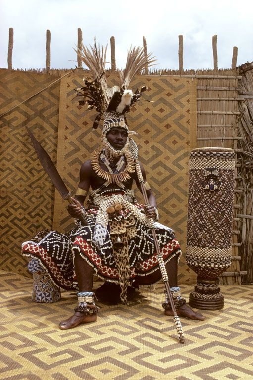 Africa   Nyim Kot a Mbweeky III wearing royal dress 'labot latwool'; royal headdress known as 'Shody'; necklace 'Lashyaash' made of leopard teeth; sword 'Mbombaam', lance 'Mbwoom Ambady' and other items of royal adornement. Bungamba village, Congo (DR)   © Eliot Elisofon, 1970