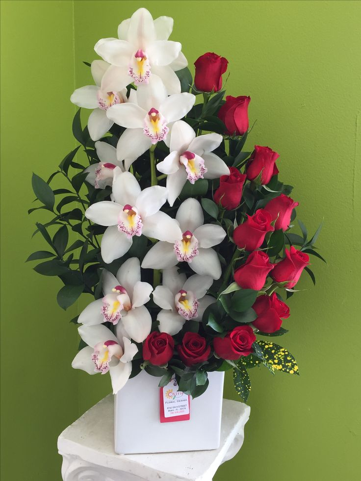 white square ceramic vase with red roses and white orchids