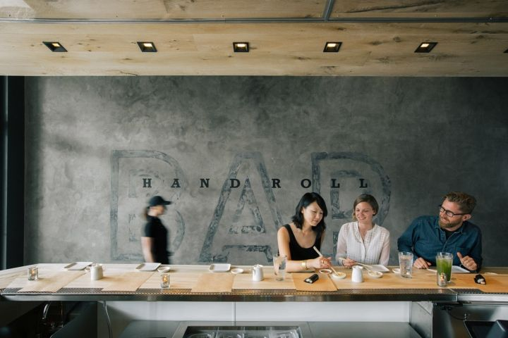 """Diners are greeted with 24-stools surrounding a U-shaped bar constructed with bleached eucalyptus wood; a team of chefs operate from behind the counter with a sculptural bleached rustic white oak """"roof"""" looming overhead with inset lighting illuminating the counter."""