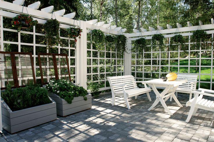 Talon vieressä oleva patio on rajattu ympäristöstä ilmavalla, pergolamaisella rakenteella. Seinäelementti kuuluu Kannustalon pihamallistoon,...