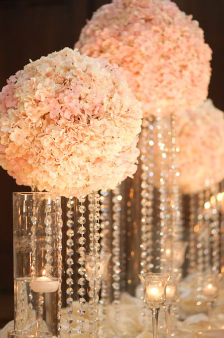 gorgeous white carnation ball and crystal centerpieces. Place the ball on a clear vase and pin crystals to the bottom of the ball, so that they can hang down inside. Use a flameless votive candle inside the vase. --- this but red flowers
