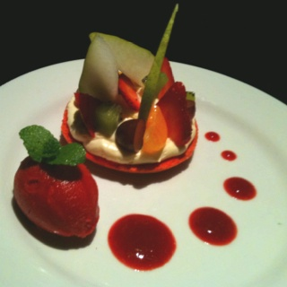 Raspberry and hibiscus macaron with vanilla cream mousse, fresh fruit salad, red fruits sorbet, and a house made raspberry and hibiscus sorbet