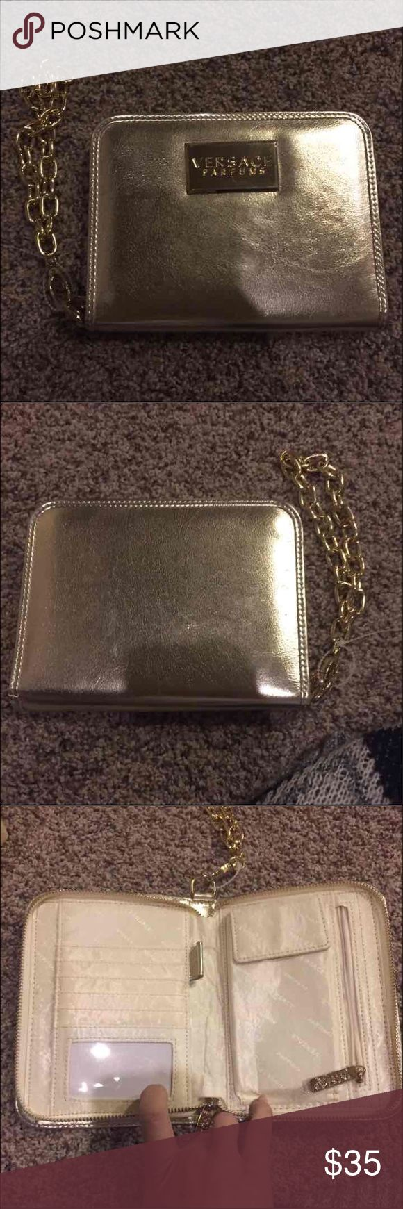 Authentic Versace gold clutch New without tags . Holds money phone cards ect.. 100% authentic . Super cute no flaws Versace Bags Clutches & Wristlets