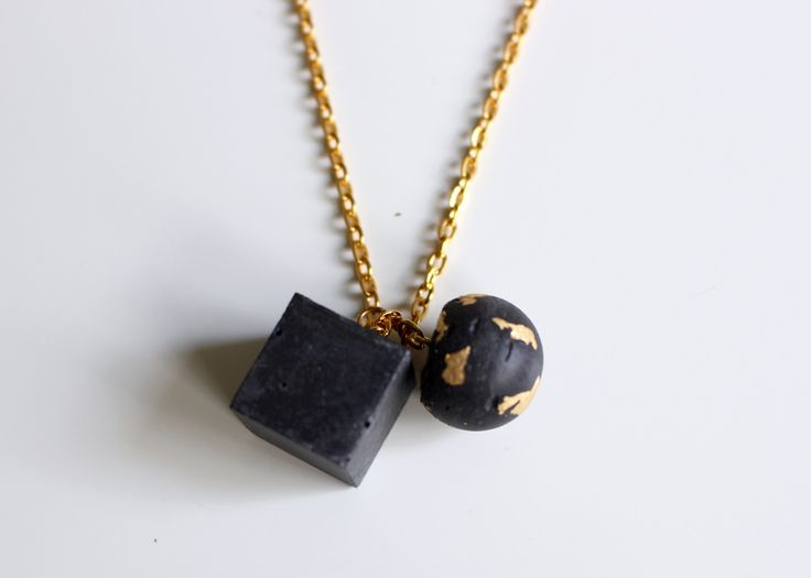 Betónová+kocka+s+guličkou+black/gold+prívesky+odliate+z+betónu+v+tvare+kocky+a+guličky,+farbené+v+procese+prípravy+čiernym+pigmentom.+Gulička+so+zalakovanou+jemnou+zlatou+fóliou.+Zaujímavá+štruktúra+betónu+zachovaná.+Na+retiazke+zlatej+farby.+Retiazka+je+dostatočne+dlhá,+je+bez+zapínania,+spojená+spojovacím+krúžkom.+Celková+dĺžka+retiazky+je+86+cm